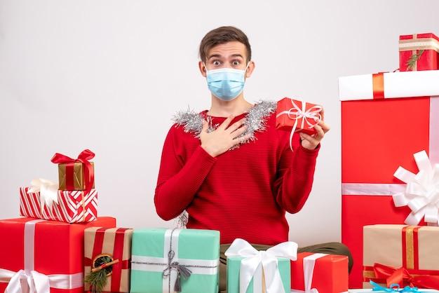 Jovem com máscara segurando um presente sentado em frente aos presentes de natal