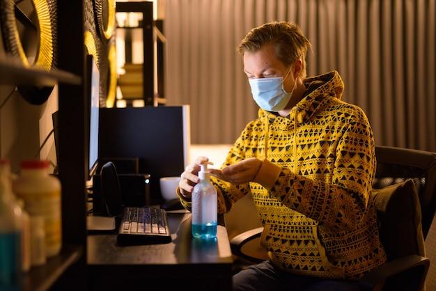 Jovem com máscara usando desinfetante para as mãos enquanto trabalha em casa à noite