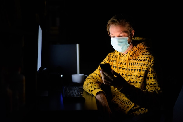 Jovem com máscara usando telefone enquanto trabalha em casa tarde da noite no escuro