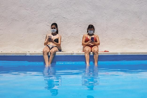 Jovem com máscaras tomando banho de sol na piscina usando o celular