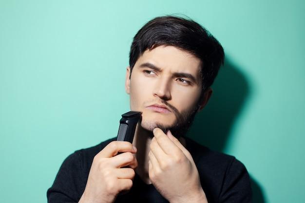 Jovem com metade do rosto raspado, segurando o aparador de barbear elétrico na parede de água menta.