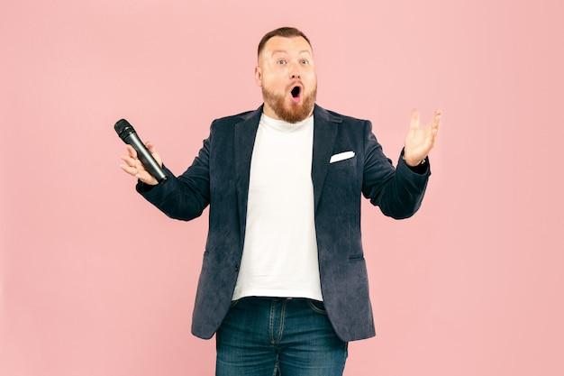 Jovem com microfone em fundo rosa, levando com microfone