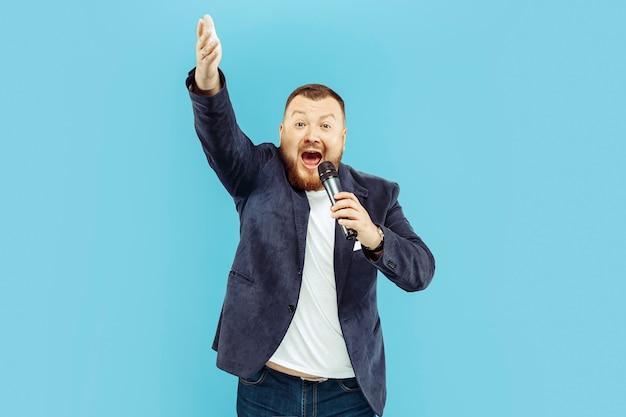 Jovem com microfone na parede azul