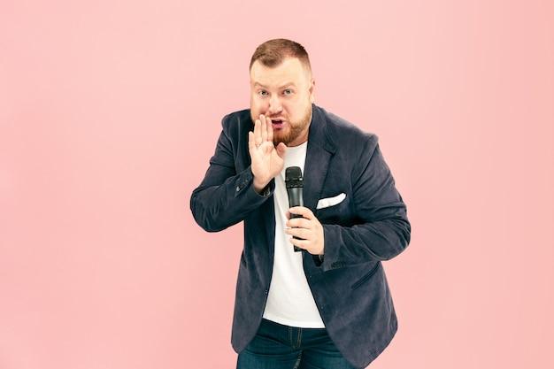Jovem com microfone no espaço rosa, conduzindo com microfone