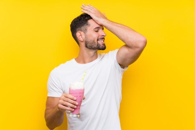 Jovem com milk-shake de morango sobre parede amarela isolada percebeu algo e pretendia a solução