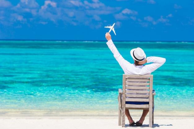 Jovem com miniatura de um avião na praia tropical