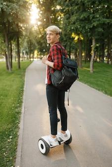 Jovem com mochila andando na mini placa do giroscópio no parque de verão.