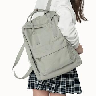 Jovem com mochila cinza de estudante