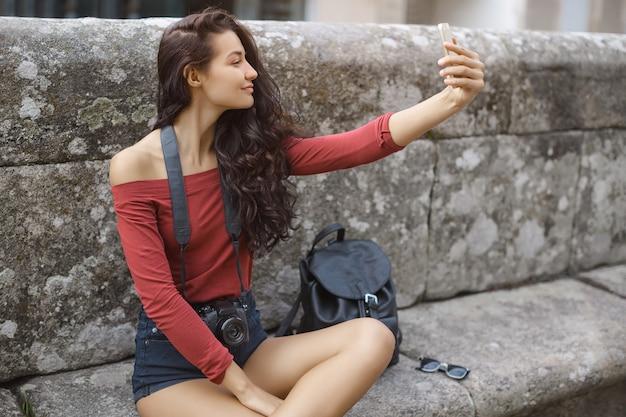 Jovem com mochila de smartphone e câmera ao ar livre. mulher feliz tirando uma selfie sentada em um banco