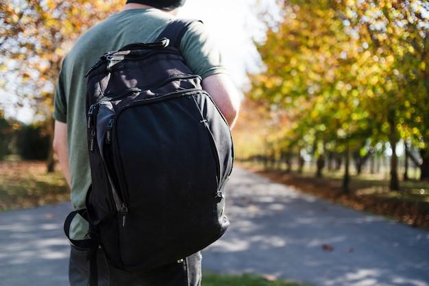 Jovem com mochila no parque