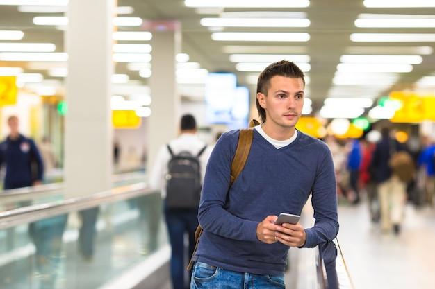 Jovem com mochila, segurando o telefone celular no aeroporto esperando o voo