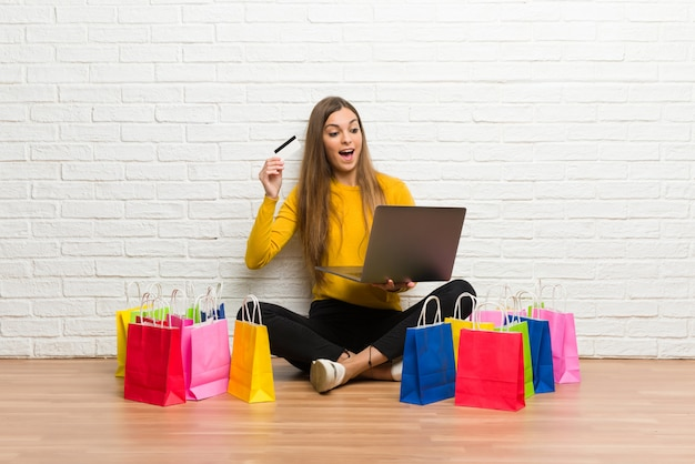 Jovem com muitos sacos de compras com laptop e cartão de crédito