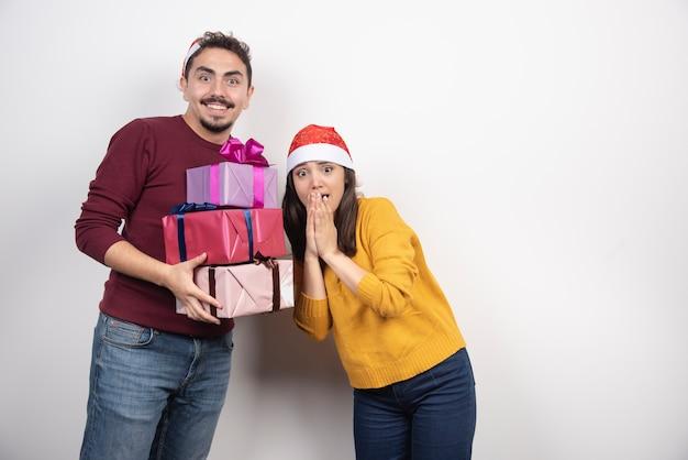 Jovem com mulher posando com presentes de natal.