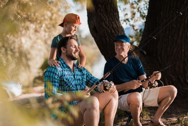 Jovem com o filho e pai pescando no rio.