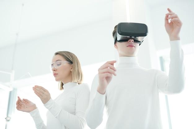 Jovem com óculos de realidade virtual testando um novo aplicativo de realidade virtual enquanto uma jovem o verifica em um tablet futurista