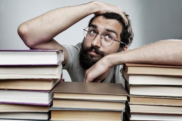 Jovem com óculos e barba se senta em uma mesa com pilhas de livros. treino e educação.