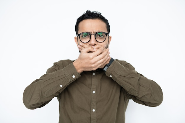 Jovem com óculos em frente à câmera e cobrindo a boca com as mãos enquanto se sente mal