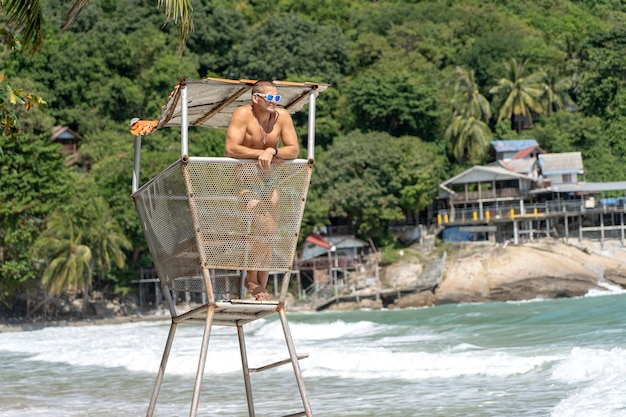 Jovem com óculos escuros em uma torre de resgate na praia tropical.