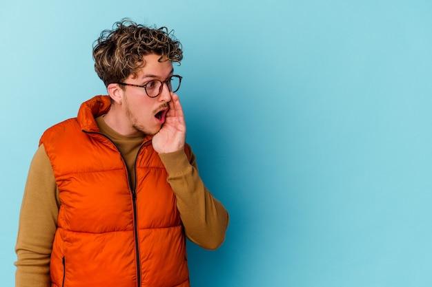 Jovem com óculos isolados na parede azul está contando uma notícia secreta sobre a frenagem e olhando para o lado