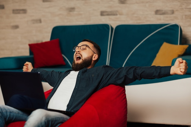 Jovem com óculos parecia cansado, com sono e bocejando enquanto estava sentado no laptop, trabalho online de negócios em casa.