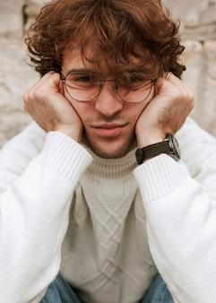 Jovem com óculos posando ao ar livre