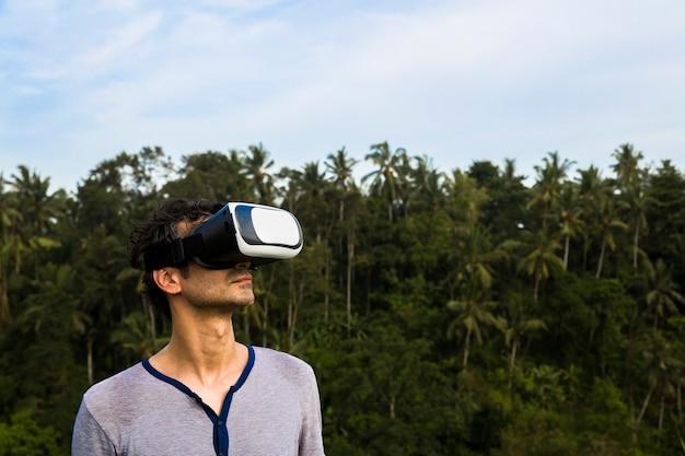 Jovem com óculos vr na floresta tropical