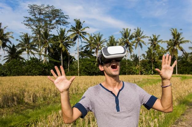 Jovem com óculos vr no campo de arroz tropical