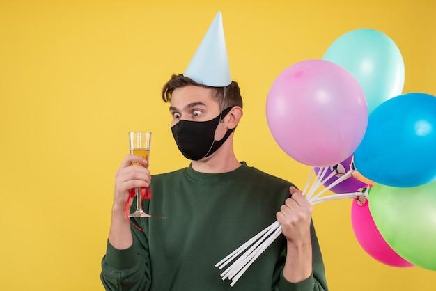 Jovem com olhos arregalados de frente e chapéu de festa e máscara preta segurando uma taça de vinho e balões amarelos