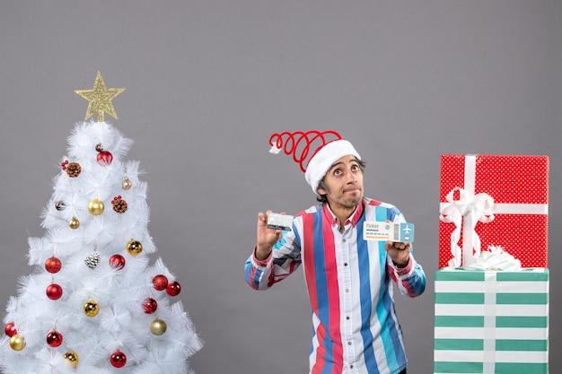Jovem com olhos curiosos segurando um cartão e um bilhete de viagem ao redor da árvore de natal e presentes