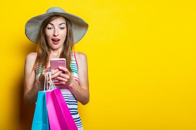 Jovem com pacotes com compras, em choque, surpresa, olha para o telefone