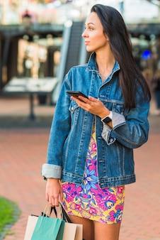 Jovem com pacotes de compras, segurando o telefone móvel no mart