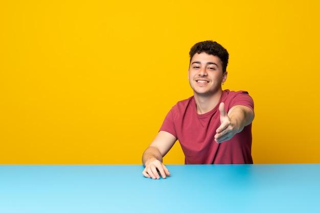 Jovem com parede colorida e mesa apertando as mãos para fechar um bom negócio