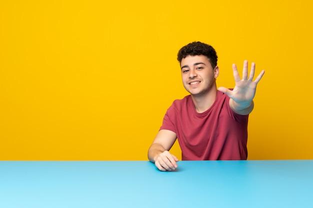 Jovem com parede colorida e mesa contando cinco com os dedos