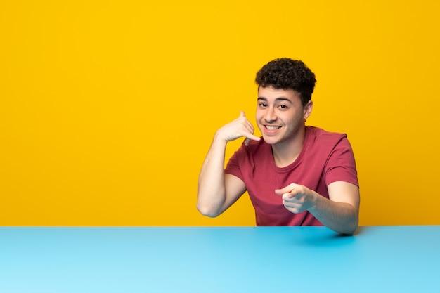 Jovem com parede colorida e mesa fazendo gesto de telefone e apontando a frente