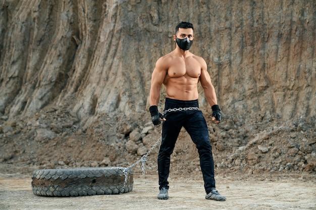Jovem com peito nu musculoso, máscara preta, segurando a corrente com um pneu grande. conceito de musculação e estilo de vida ativo.
