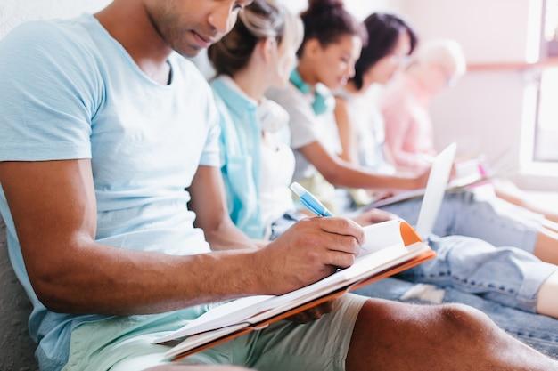 Jovem com pele morena, camisa azul, escrevendo palestra no caderno, sentado ao lado de colegas de universidade. retrato interno de alunos estudando juntos na biblioteca da faculdade.