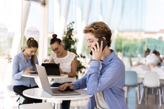 Jovem com piercings falando em um telefone móvel, sentado em uma mesa com um laptop