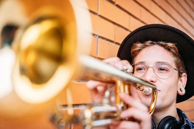 Jovem com piercings tocando trompete.