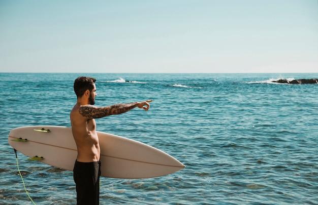 Jovem com prancha de surf na praia, apontando para a água