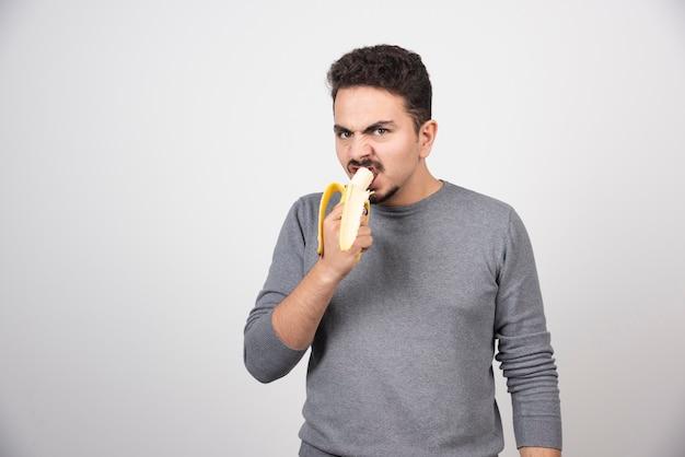 Jovem com raiva comendo uma banana sobre uma parede branca.