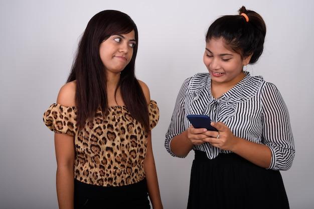 Jovem com raiva de uma jovem adolescente feliz sorrindo enquanto usa o telefone celular
