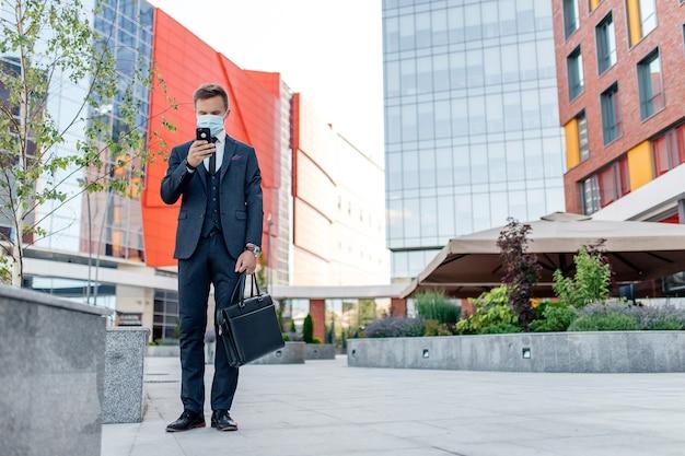 Jovem com roupa formal usando smartphone na cidade, máscara médica, mensagens no celular em pé na rua perto de edifícios contemporâneos