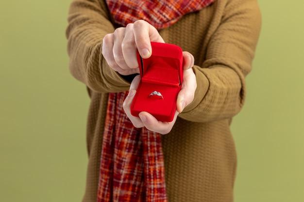 Jovem com roupas casuais com lenço no pescoço mostrando uma caixa vermelha com anel de noivado conceito do dia dos namorados em pé sobre a parede verde