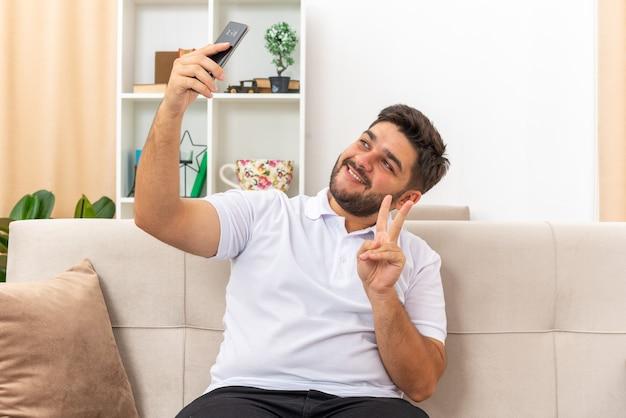 Jovem com roupas casuais fazendo selfie usando smartphone feliz e positivo mostrando o sinal de v sorrindo, sentado em um sofá em uma sala iluminada