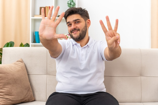 Jovem com roupas casuais, parecendo feliz e sorridente, mostrando o número oito sentado em um sofá em uma sala iluminada
