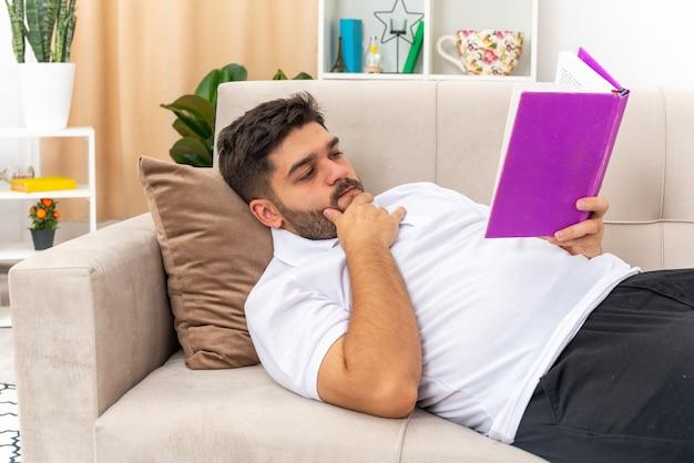 Jovem com roupas casuais, segurando um livro lendo com uma cara séria, passando o fim de semana em casa deitado em um sofá na sala de estar iluminada