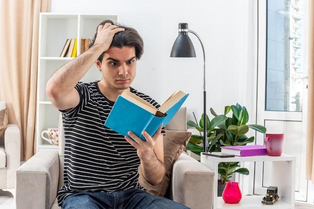 Jovem com roupas casuais segurando um livro lendo e parecendo perplexo, sentado na cadeira em uma sala iluminada