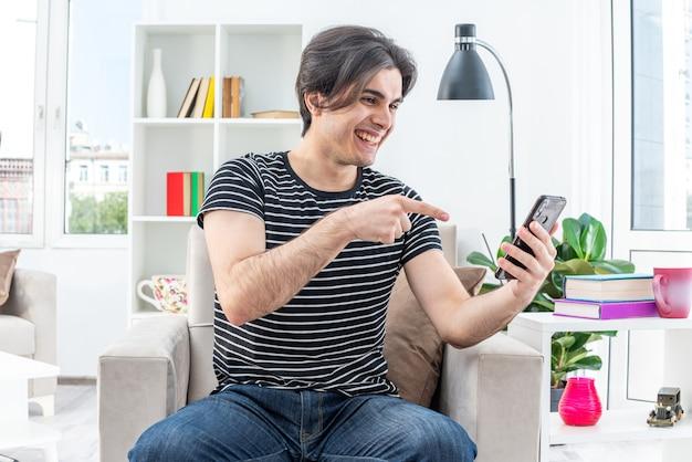 Jovem com roupas casuais segurando um smartphone, olhando para ele, feliz e alegre, sentado na cadeira na luz da sala de estar