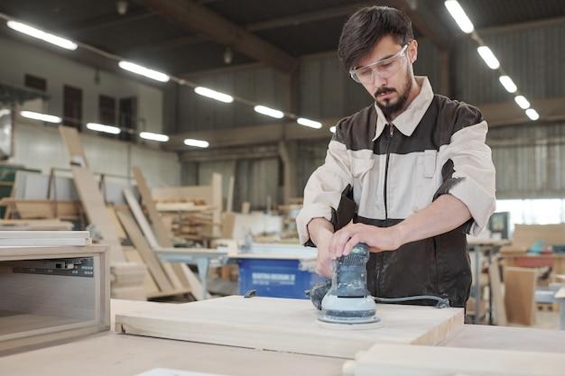Jovem com roupas de trabalho e óculos de proteção, curvado sobre a bancada enquanto processa a superfície da placa de madeira