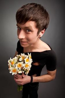 Jovem com roupas pretas modernas segurando buquê de flores de narciso nas mãos sobre cinza